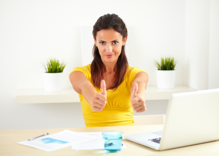 pleased: Hispanic female working as a boss in a business company while showing you her pleased satisfaction - copyspace