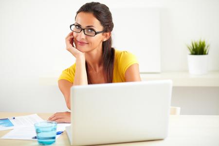 secretarias: Trabajador hispano alegre con gafas que usa su ordenador en la oficina
