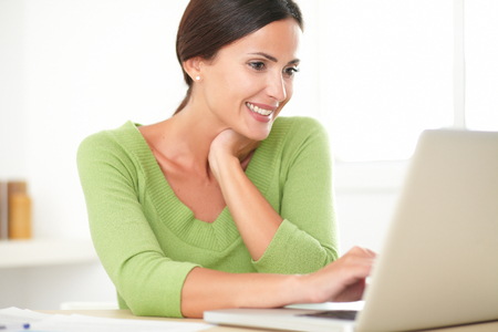 charming business lady: Pretty latin lady in green shirt smiling while working on her laptop at home