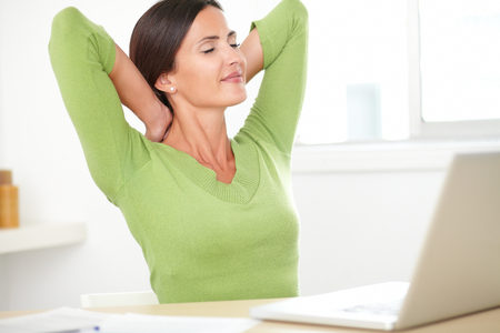 taking a break: Elegant hispanic woman in green shirt taking a break from work and sitting at home Stock Photo