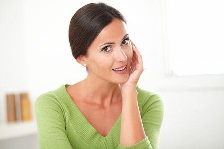 Lovely sophisticated lady in green shirt with natural beauty smiling at home