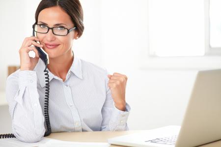 llamando: Secretario de la sociedad bonita con los vidrios alegremente conversando por teléfono mientras se utiliza el ordenador en la oficina