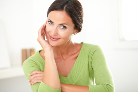 attractive charismatic: Charming adult woman in green shirt smiling with satisfaction at indoor Stock Photo