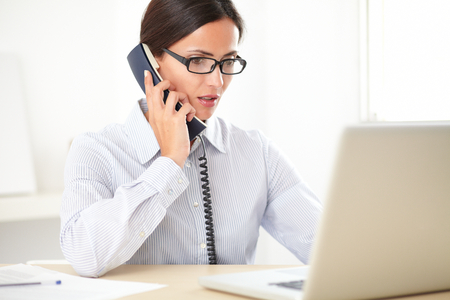 secretary phone: Adult female employee with glasses doing customer service and using her laptop at the workplace Stock Photo