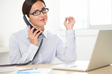 phone professional: Adult secretary with glasses talking on the phone while smiling in her office