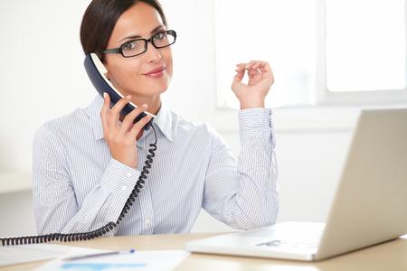 llamando: Secretaria adulta con gafas hablar por teléfono mientras sonreía en su oficina