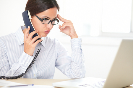 conversing: Pretty female executive with glasses conversing on the phone while looking stressed in the office Stock Photo