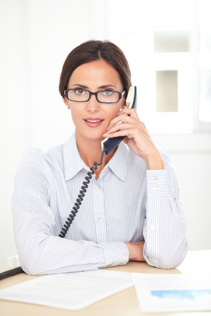 conversing: Adult businesswoman with spectacles conversing on the phone in her office
