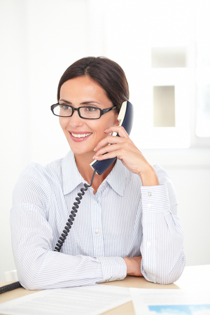 Latin receptionist with spectacles conversing on the phone while smiling at her workplace