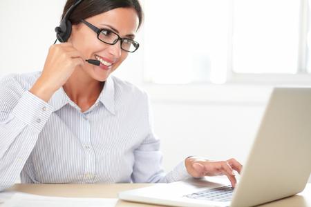secretaria: Secretaria de la mujer joven con los auriculares que hacen el servicio al cliente en un callcenter
