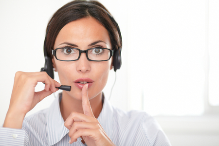 shushing: Pretty employee in blue shirt speaking on the headset while shushing and looking at you - copyspace