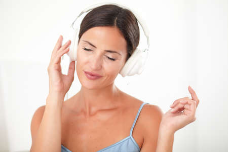 chilling out: Smart woman with closed eyes in blue blouse chilling out by listening to music at her house