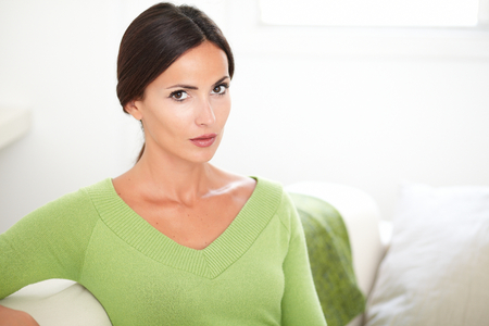 feminity: Beautiful woman with confidence and with caucasian ethnicity looking at the camera at indoors - copy space