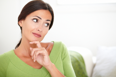 caucasian ethnicity: Confident woman with caucasian ethnicity thinking while looking away at indoors - copy space
