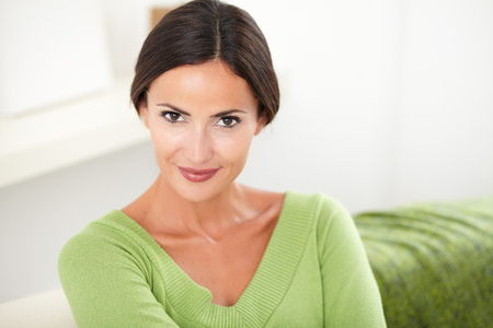 confidently: Young woman in green shirt confidently smiling at the camera at indoors - copy space