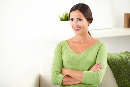 feminity: Confident young caucasian woman with arms crossed looking away and smiling at indoors - copy space