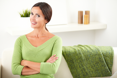 feminity: Beautiful woman with toothy smile looking at the camera while crossing her arms at home - copy space