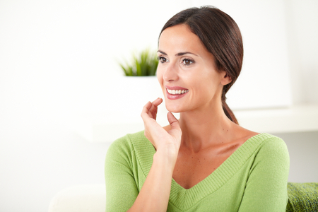 hair back: Young woman with hair back smiling and looking away with confidence at indoors - copy space