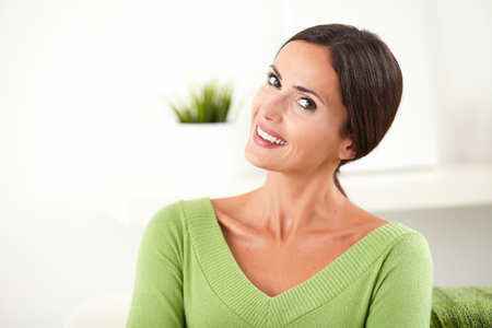 feminity: Smiling caucasian young woman in green shirt looking at the camera at indoors - copy space Stock Photo