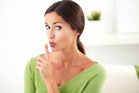 focus in foreground: Caucasian woman in green shirt making the silence gesture with focus on foreground Stock Photo