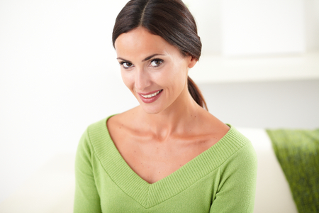 Young confident woman with toothy smile looking at the camera while contemplating at indoors Stock Photo