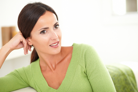 feminity: Young beautiful woman with brown hair looking away and wondering at indoors - copy space Stock Photo