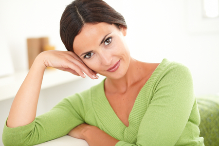 feminity: Young beautiful woman with hand on face looking at the camera while smiling with confidence at home
