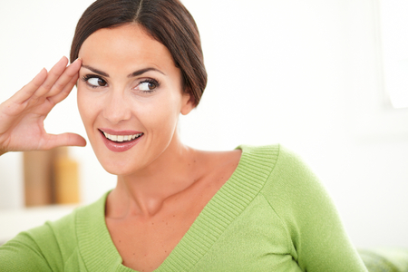 Beautiful woman with toothy smile looking away and smiling with confidence at home - copy space