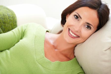 relajado: Mujer relajada joven en una camisa verde que mira a la c�mara con una sonrisa con dientes Foto de archivo