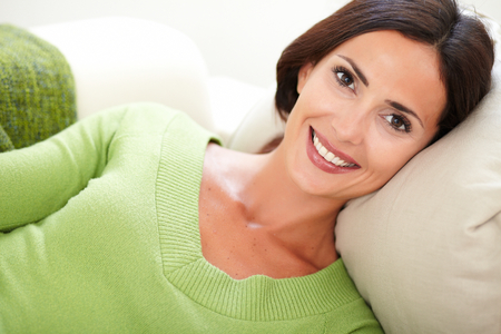 relaxation: Young relaxed woman in a green shirt looking at the camera with a toothy smile Stock Photo
