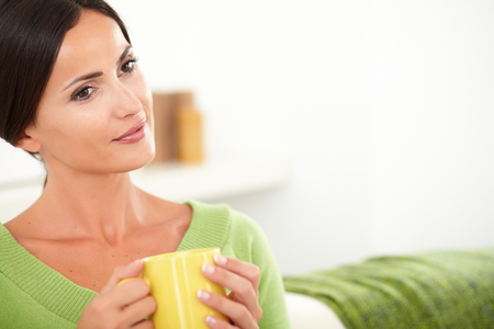 contemplative: Contemplative woman with brown hair sitting in the house and holding a yellow mug - copy space