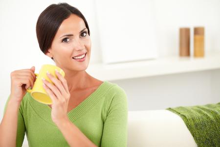capelli castani: Relaxed donna con i capelli lisci castani detiene una tazza gialla di caff� al chiuso - copia spazio