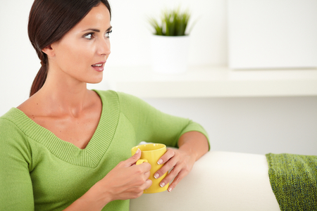 focus on the foreground: Peaceful woman in a green shirt holding a yellow mug while looking away - focus on foreground Stock Photo