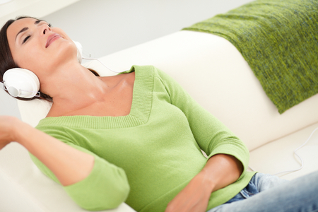 head back: Relaxed woman resting with eyes closed while listening to music on headphones with her head back Stock Photo