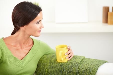 caucasian ethnicity: Relaxed woman of caucasian ethnicity sitting indoors and looking away