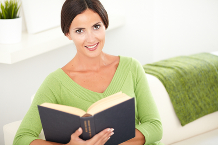 caucasian ethnicity: Young woman of caucasian ethnicity sitting inside the house and reading a book - elevated view