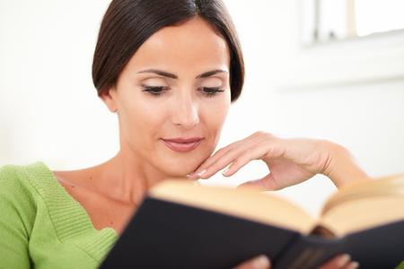 capelli castani: Testa e spalle ritratto di una donna tranquilla, con i capelli castani lettura di un libro a chiuso