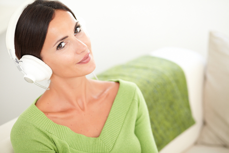 elevated view: Attractive calm woman with straight brown hair listening to music while sitting indoors - elevated view