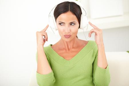 manos levantadas: Mujer atractiva que escucha la música con las manos levantadas en los auriculares mientras se mira lejos - espacio de la copia