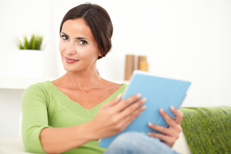 focus on the foreground: Relaxed young female holding a tablet while sitting inside the house - focus on foreground