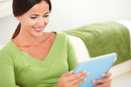 waist up: Waist up portrait of a smiling young woman using a tablet while sitting indoors - focus on foreground