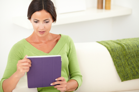 waist up: Waist up portrait of a thoughtful young woman holding a tablet while sitting indoors - copy space