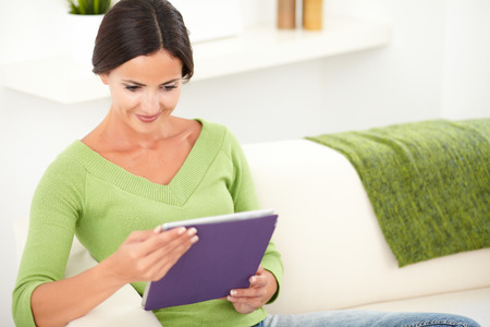 caucasian ethnicity: Attractive lady of caucasian ethnicity holding a tablet at indoors - copy space Stock Photo