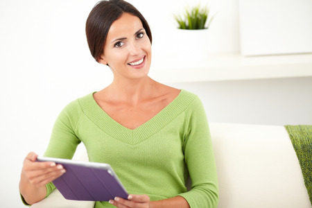 waist up: Waist up portrait of a relaxed lady with brown hair smiling at the camera while holding a tablet