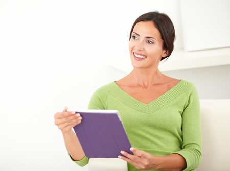 waist up: Waist up portrait of a smiling young woman holding a tablet while looking away - copy space Stock Photo