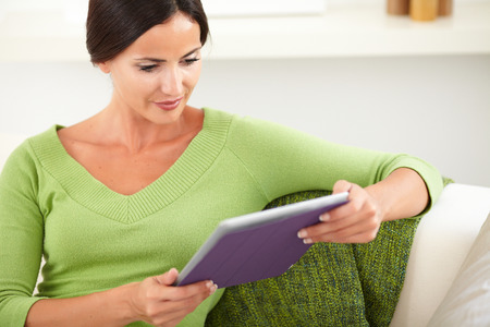 waist up: Waist up portrait of a caucasian woman in a green tank top using a tablet indoors