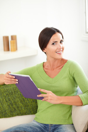 three quarter length: Three quarter length portrait of an attractive woman smiling at the camera while holding a tablet Stock Photo