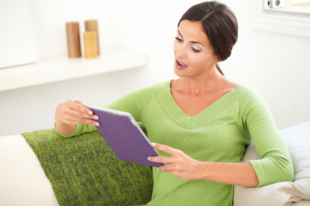 waist up: Waist up portrait of a surprised woman looking at a tablet with her mouth open