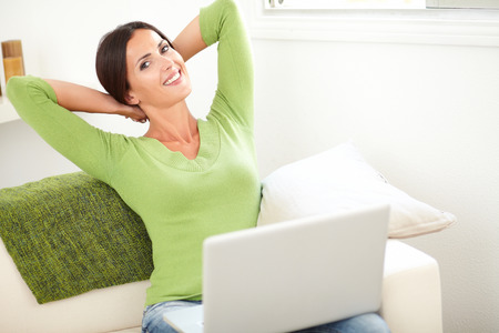 sit up: Calm woman relaxing with her hands behind her head while holding a laptop Stock Photo