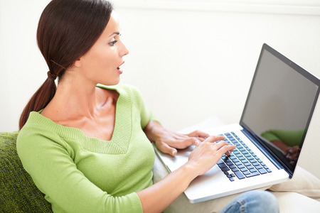 waist up: Waist up portrait of a young woman looking surprised at her laptop screen